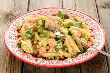 Creamy pasta with salmon and parsley in red plate