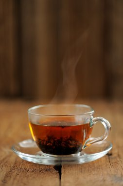 Shu puerh tea brewed steaming in glass cup on wooden background