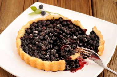 Juicy blueberry tart cut in square white plate with fork and wil