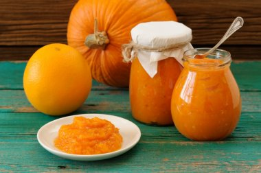Homemade sweet pumpkin jam in white plate and in glass jars with