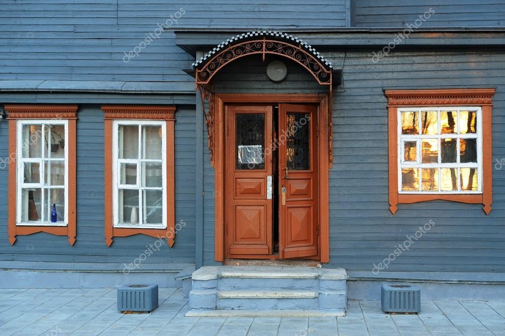 Facciata della casa in legno grigio blu con marrone porta for Disposizione della casa aperta