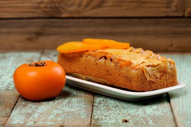 Homemade persimmon cake with fresh persimmon on old turquoise ta