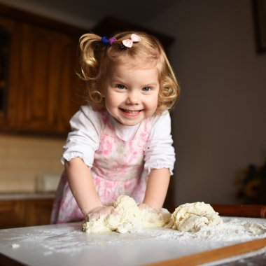 pretty little girl having fun kneads dough