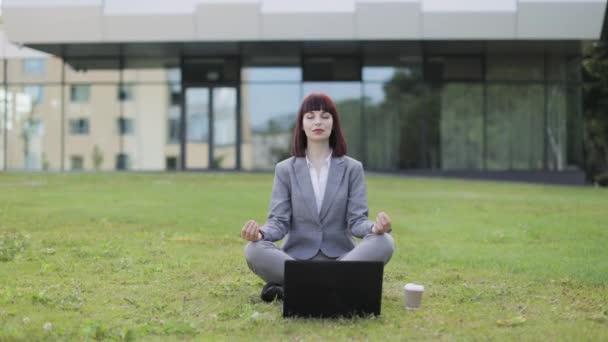Csinos nő gyakorló jóga, ül csukott szemmel kívül iroda zöld fű