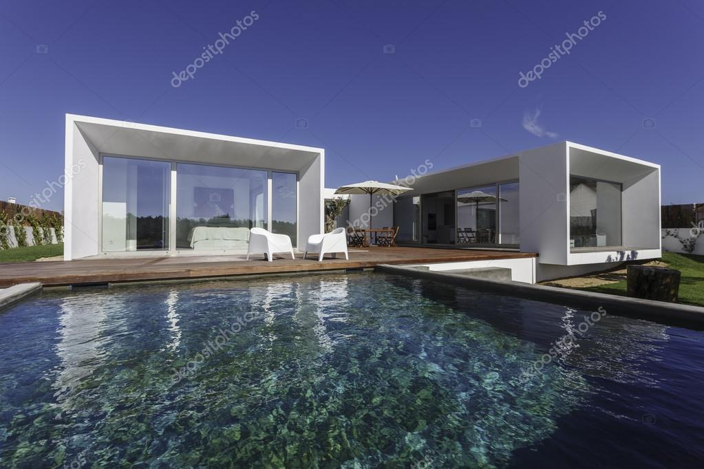 Modern house with garden swimming pool and wooden deck stock photo