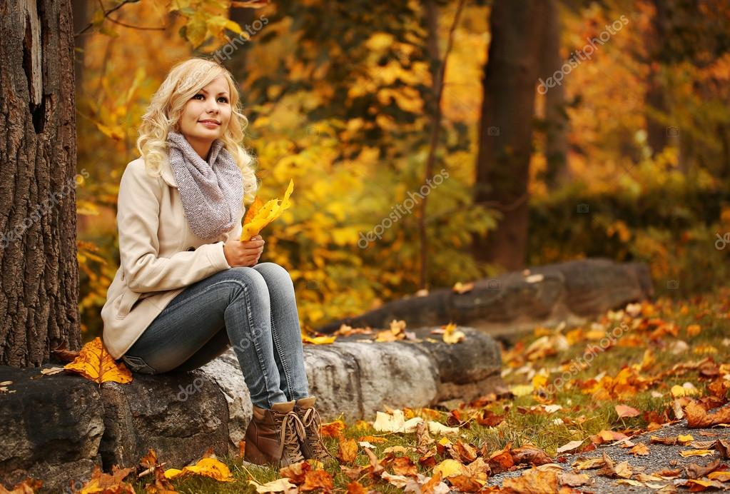 Autumn Woman. Fall. Blonde Beautiful Girl with Yellow Leaves