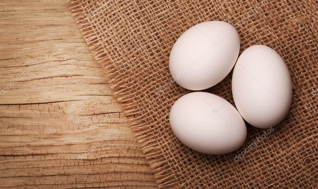 White eggs on burlap over wooden background