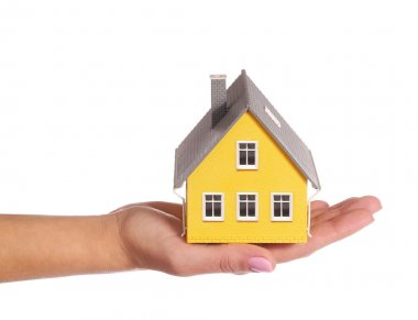 Tiny house in female hand isolated on white