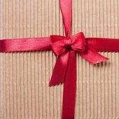 Dárkové krabičce zabalený červenou stuhou s lukem, pohled shora