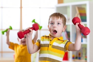 Funny kids boys exercising with dumbbells at home. Healthy life, sportive children.