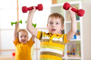 Little children boys exercising with dumbbells at home. Healthy life, sportive kids.