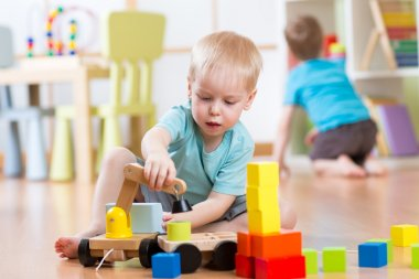 Child boy plays with building blocks and car sitting on the floor in kindergarten