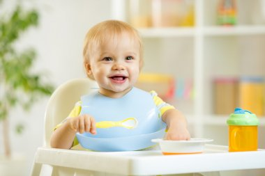 Happy baby kid boy eating food itself with spoon