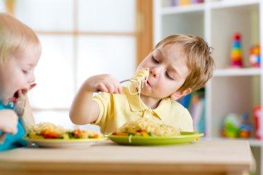 Children eating healthy food in kindergarten or nursery