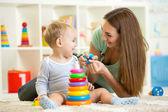 Roztomilý matka a dítě chlapec spolu hrají doma vnitřní
