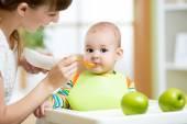Šťastná matka lžíce krmit své dítě dítě