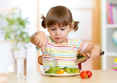 Kid eating healthy food at home or kindergarten