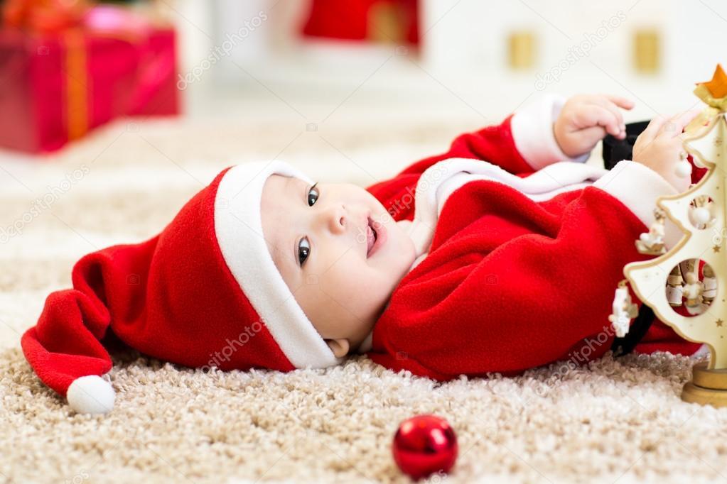 Baby boy weared Santa holding christmas ball