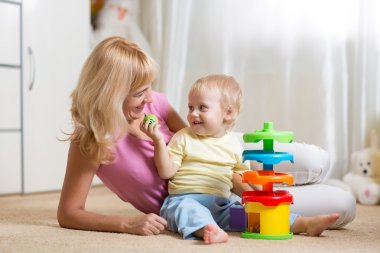 mom and her child playing with colorful logical toy