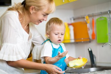 Mother And Son Cleaning Dishes Together