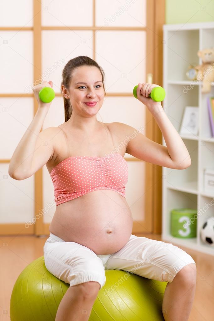 Mujer embarazada haciendo ejercicios de fitness sentado en pelota de  gimnasio que ejercitarse con pesas — 6fad6e83b891