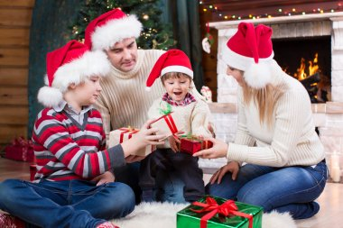 Happy family in red hats with gifts sitting at Christmas tree near fireplace
