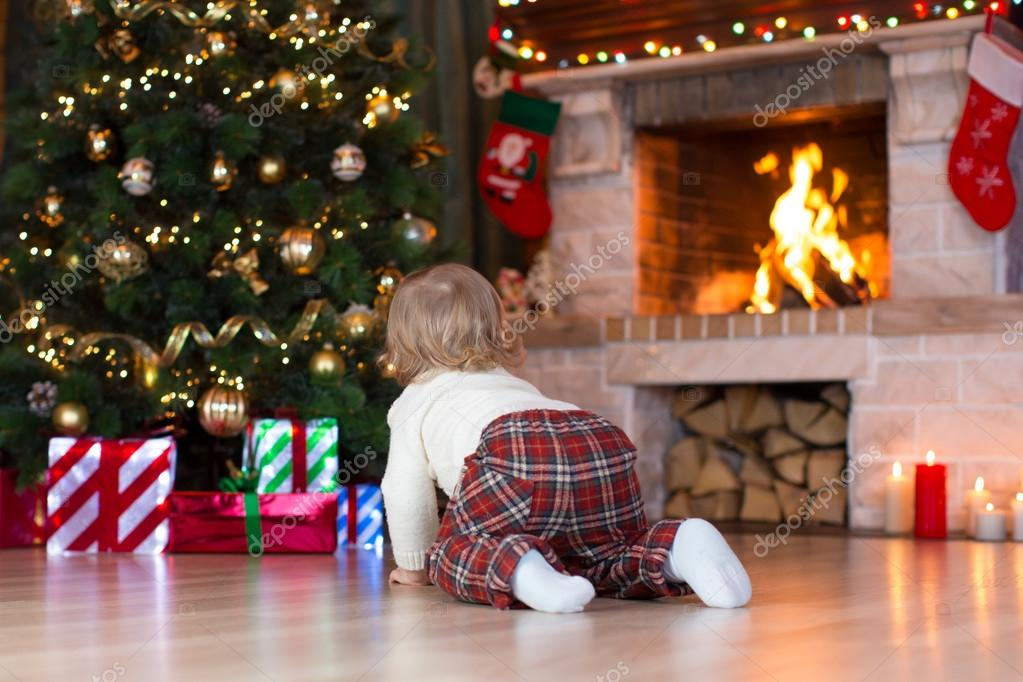 Child crawling to gifts lying under Christmas tree