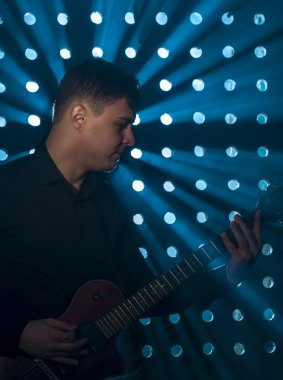 Male musician playing on electric guitar