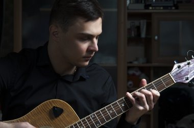 Male musician playing on guitar