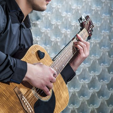 Closeup of man's hands playing on acoustic guitar