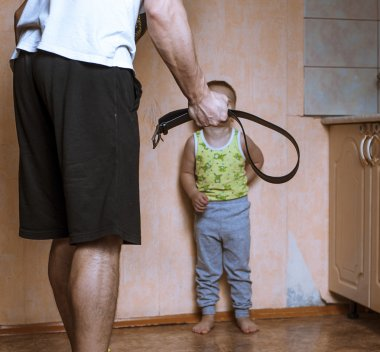 Angry father with belt and scared child
