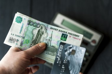 Russian ruble bills and banking card in female hands