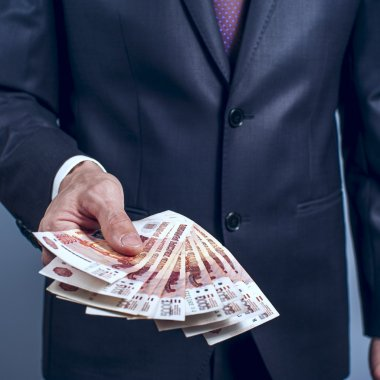Man in a suit holding Russian rubles