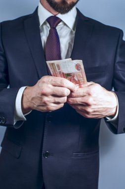 Bearded man in suit holds Russian rubles