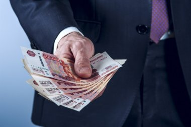 Man in a suit holds Russian rubles