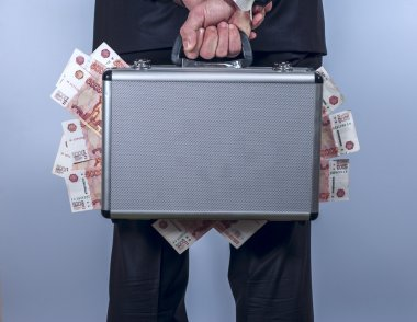 Man holds a suitcase full of money behind the back