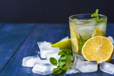 Glass of lemonade with mint leaves and ice cubes