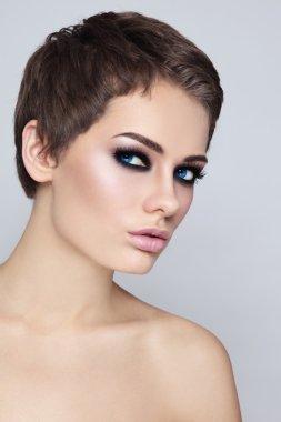 woman with stylish haircut and smoky eyes