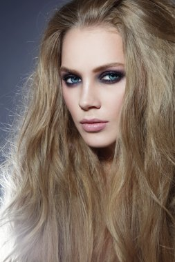 woman with long blonde hair and smoky eyes
