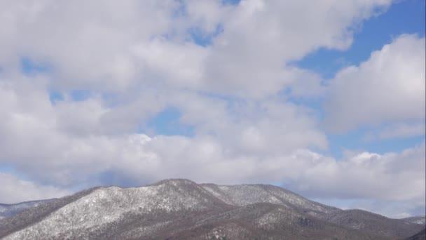 Modrá obloha bílé mraky nad zasněženými horami. Nadýchané bílé mraky. Cumulus cloud scape timelapse. Časová prodleva zimní modré oblohy. Dramatická majestátní modrá obloha. Měkká bílá mračna. Čas mraků