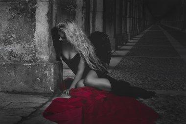 Fallen angel in dress with black wings