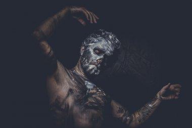 Muscular naked man covered with paint