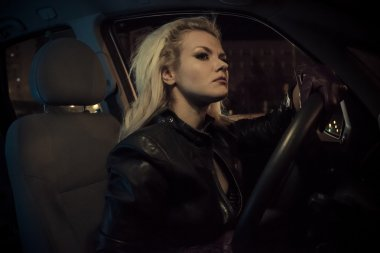 Blonde in car driving at night