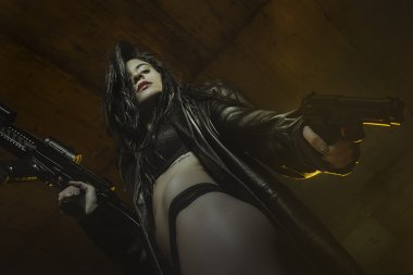 violence, brunette girl dressed in black leather with guns and p