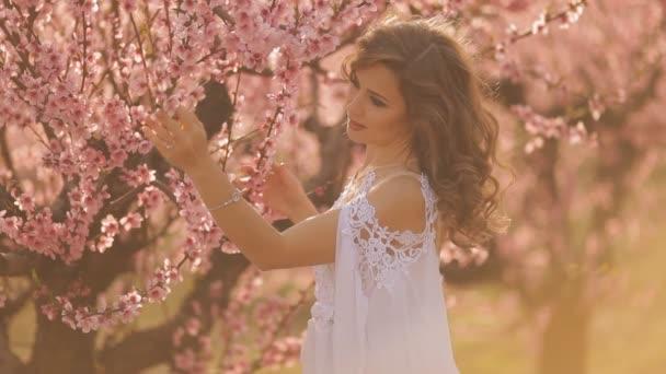 Young beautiful blonde woman in blooming garden.
