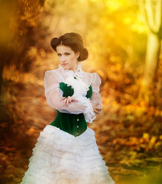 Beautiful girl in retro style is walking in the autumn forest