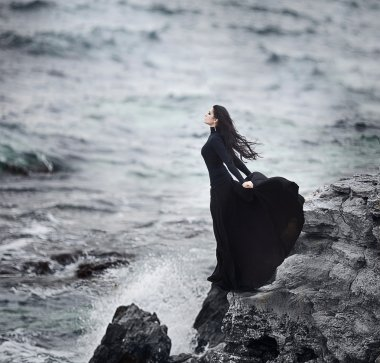 Beautiful girl in black on the sea