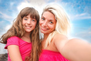 Little girl and her mom having some fun at the beach and taking a selfie with a smartphone stock vector