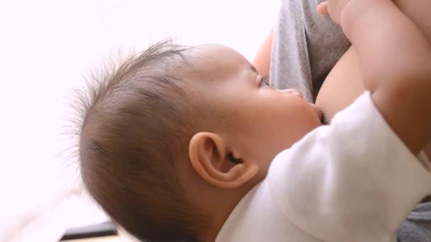Mutter stillt ihr Neugeborenes neben Fenster
