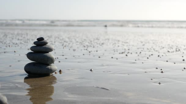 Rovnováha skal na mořském pobřeží, kameny u vln mořské vody. Pyramida z oblázků na písčitém břehu